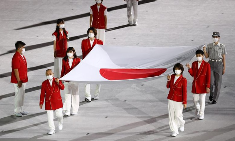 The flag of Japan is carried ahead of being raised during the opening ceremony. — Reuters
