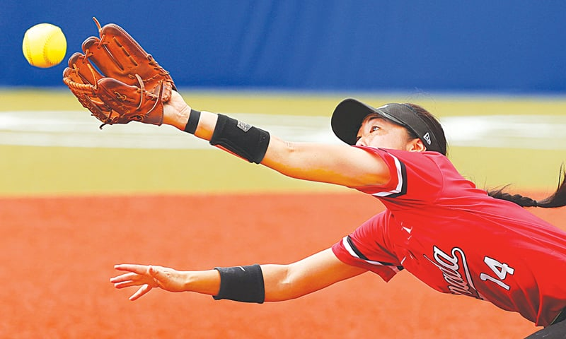 JANET Leung of Canada reaches for the ball during the women's softball opening-round match against the US at the Azuma Baseball Stadium.—Reuters