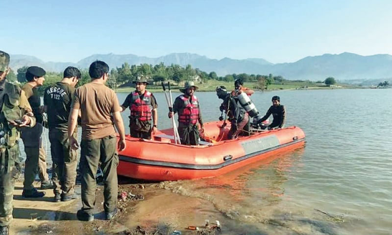 Rescue workers use a raft to search for persons missing in the Bajaur boat accident. — Dawn