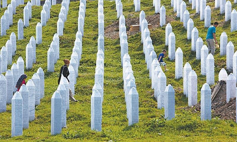In this file photo, Bosnian people visit graves at a memorial centre in Potocari near Srebrenica, 150 kilometres north-east of Sarajevo, Bosnia. — AP