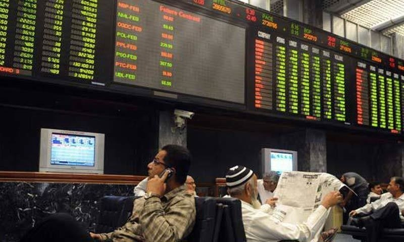 Pakistani stockbrokers watch the latest share prices on a digital board during a trading session at the Karachi Stock Exchange (KSE). — Dawn/File