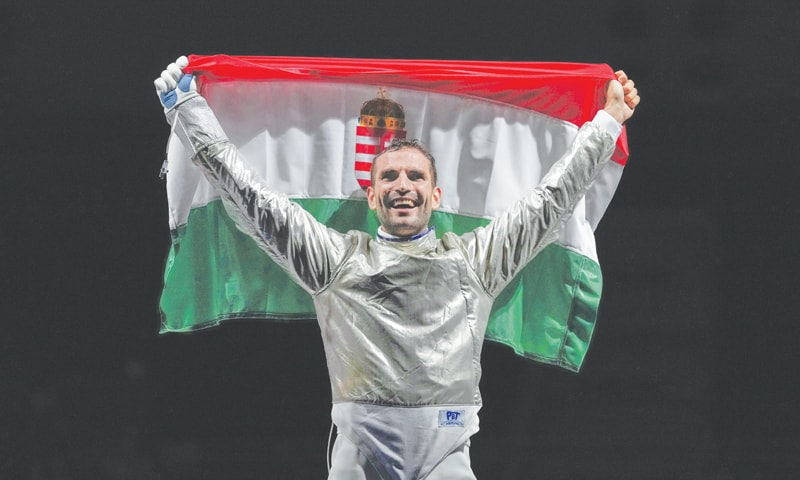ARON Szilagyi of Hungary celebrates with his national flag after winning the gold in the men's individual final Sabre competition on Saturday.—AP