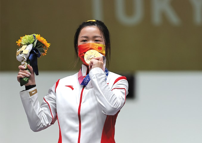 FIRST GOLD MEDAL WINNER: Yang Qian of China celebrates on the podium after winning the women's 10m Air Rifle final at the Asaka Shooting Range on Saturday. —Reuters