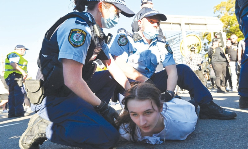 SYDNEY: Police officers detain a protester during an anti-lockdown rally on Saturday. — AFP