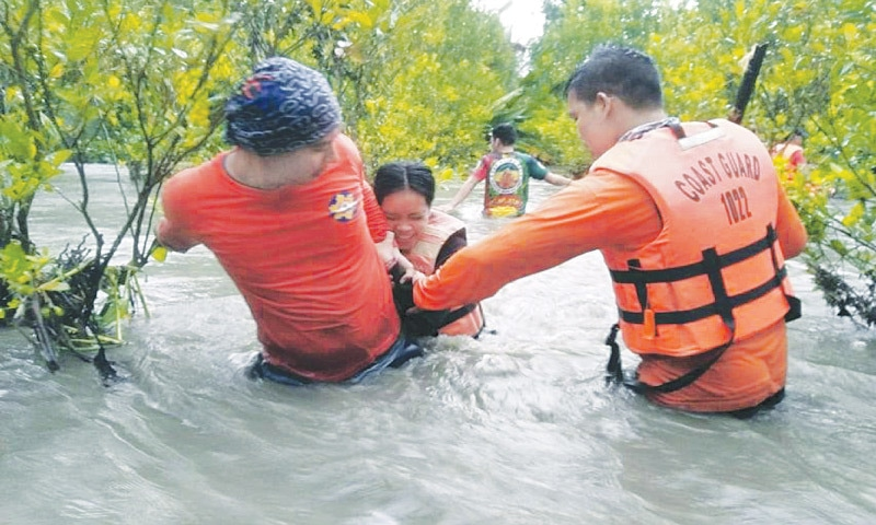 In this photo provided by the Philippine Coast Guard, residents wade along floodwaters as they are evacuated to safer grounds in Naujan, Oriental Mindoro province, central Philippines. — AP