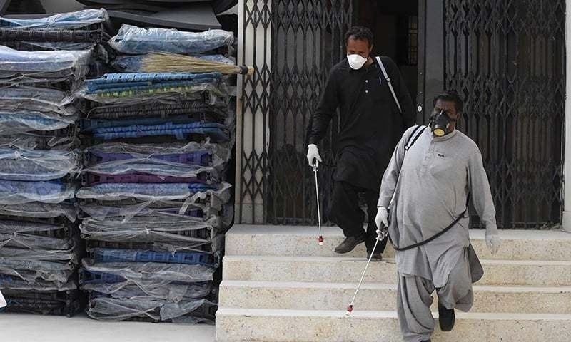 Workers of the Provincial Disaster Management Authority (PDMA) arrive to spray disinfectant at a quarantine camp in Quetta. — AFP/File