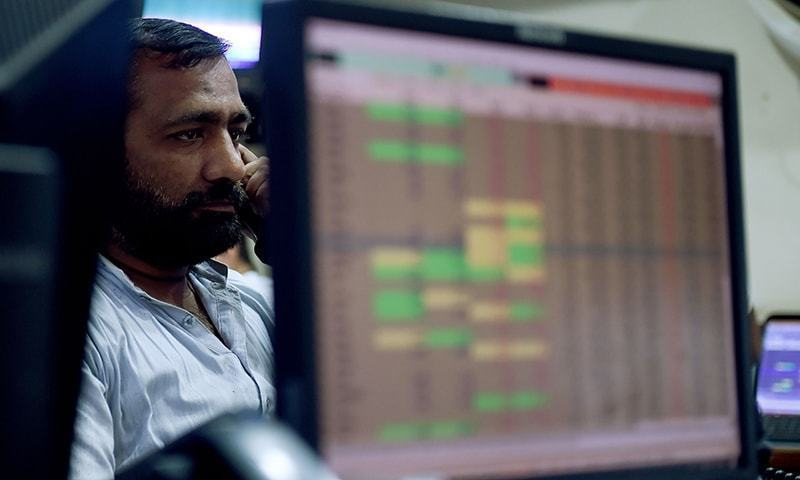 A Pakistani stockbroker looks at share prices on a computer monitor during a trading session at the Pakistan Stock Exchange (PSX) in Karachi. — AFP/File