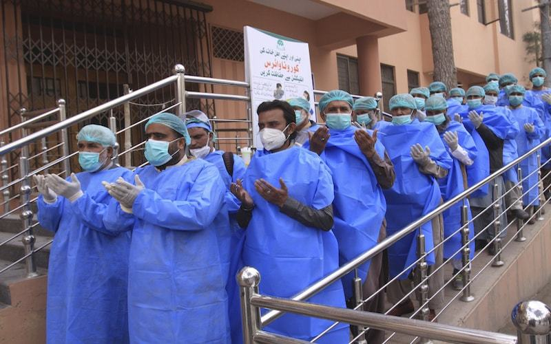 Hospital staff pray before joining their shift, outside a hospital setup for coronavirus patients.  — AP/File