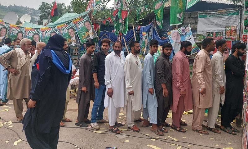 Voters queue up at Muzaffarabad's Saheli Sarkar school polling station on Sunday. — Photo by Tariq Naqash