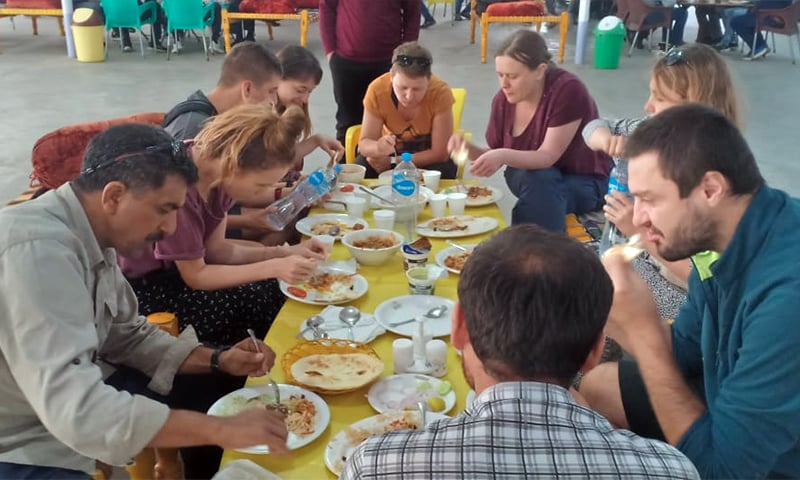 Foreign tourists enjoy a meal in Kaghan valley. — Photo provided by author