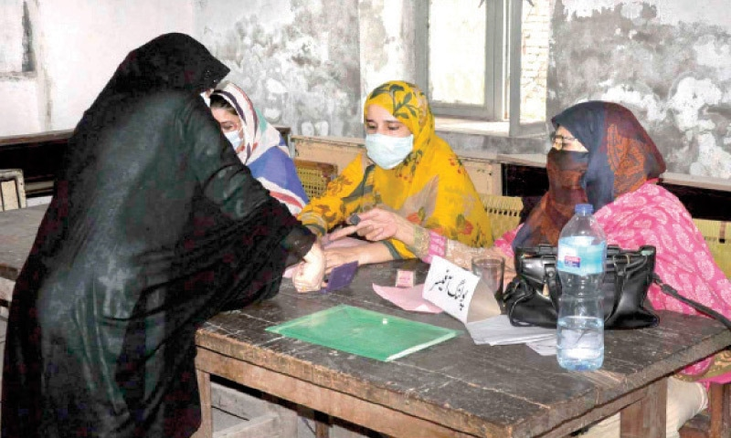 A voter presses her thumb on an ink pad at a polling station set up in Rawalpindi for the AJK election on Sunday. — APP