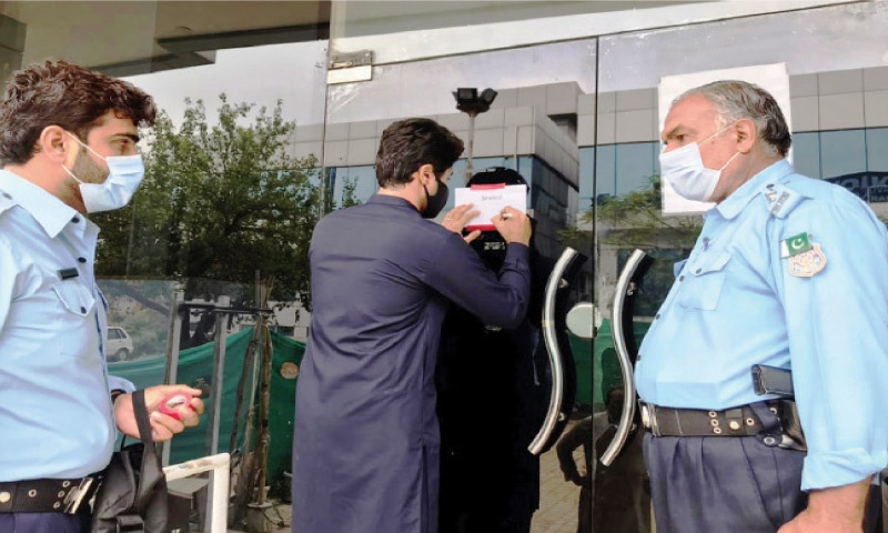 An official of the capital administration seals the office of Therapyworks on the orders of Deputy Commissioner Hamza Shafqaat in Islamabad on Sunday. — White Star