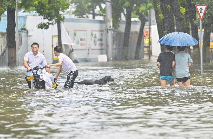 PEOPLE wade through a flooded street in Ningbo, a town in eastern Zhejiang province.—AFP