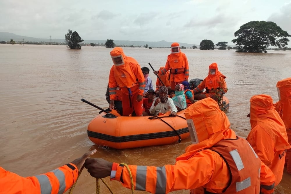 Members of National Disaster Response Force (NDRF) evacuate people from a flooded area to safer places in Balinge village, Kolhapur district, in the western Indian state of Maharashtra on July 25. - Reuters
