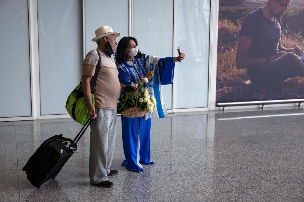 An Israeli tourist has a selfie with a hostess upon arrival at at the Marrakech-Menara International Airport on the first direct commercial flight between Israel and Morocco, on June 25. — AFP