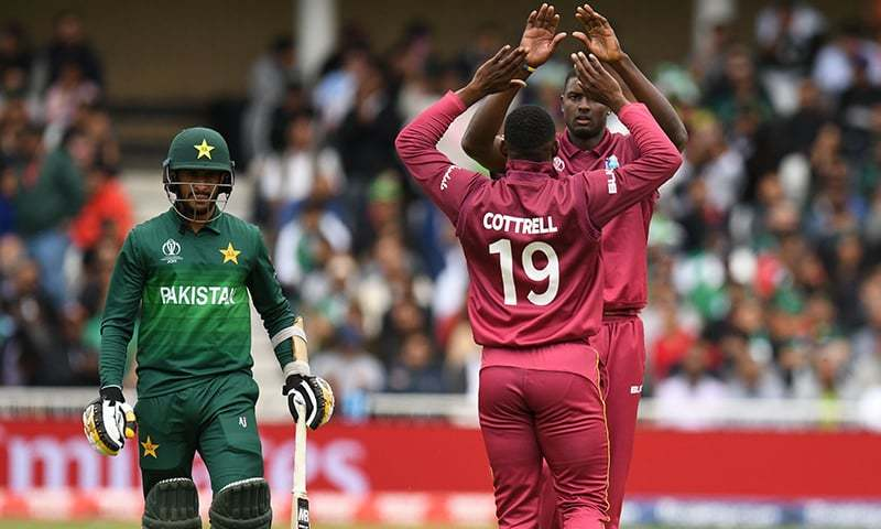 Hasan Ali (L) walks back to the pavilion after getting out for 1 run to the bowling of West Indies' captain Jason Holder (R), caught by West Indies' Sheldon Cottrell (C) during the 2019 Cricket World Cup group stage match between West Indies and Pakistan at Trent Bridge in Nottingham, central England, on May 31, 2019. — AFP
