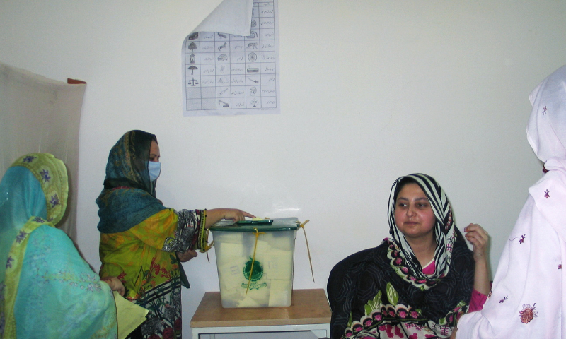 A woman casts her ballot at a polling station in Muzaffarabad, Azad Jammu and Kashmir on Sunday. — Reuters