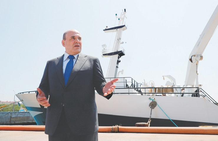 VLADIVOSTOK: Russian Prime Minister Mikhail Mishustin visits a fish processing plant on a Pacific island also claimed by Japan.—AP