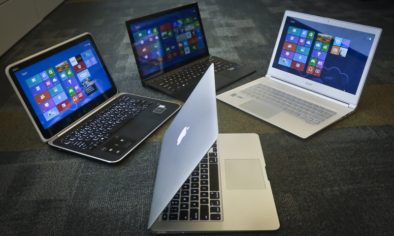 A MacBook Air from Apple, bottom center, a Vaio Pro 13 from Sony, top left, an Aspire S7 from Acer, center, and an XPS 12 from Dell, right, are displayed for a photograp. — AP/File