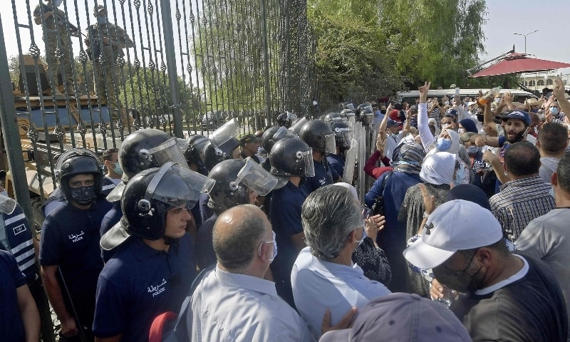 Tunisian security officers hold back supporters of the country's Islamist Ennahda party during a protest outside the parliament building in the capital Tunis on July 26. — AFP