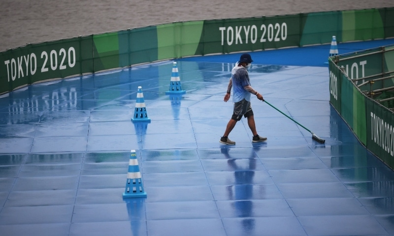 A worker prepares the track for competition during rainy weather on July 27. — Reuters