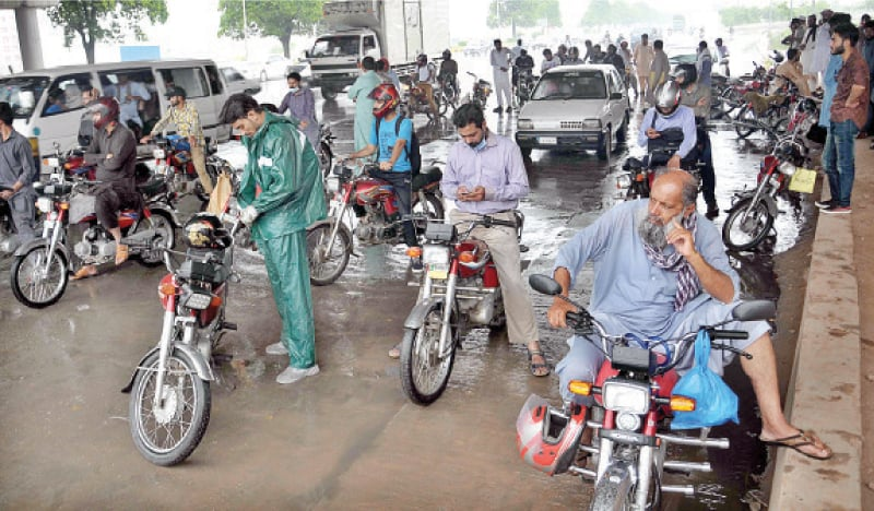 Motorcyclists wait under a bridge during rain in Islamabad on Tuesday. — APP