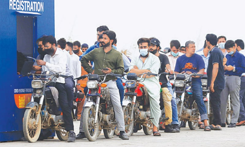 MOTORCYCLISTS queue up to get registered for the Covid-19 vaccine on Tuesday at a drive-through facility set up by the Sindh government in Clifton.—Shakil Adil/White Star