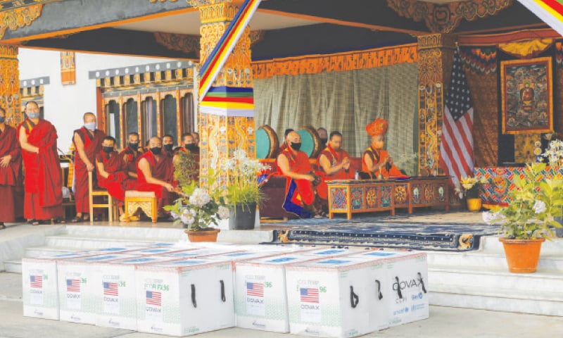 MONKS perform prayers after 500,000 doses of Moderna  vaccine gifted by the United States landed at Paro international airport.—AP