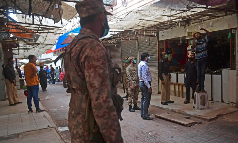 Security officials arrive at a market to enforce an evening lockdown imposed amid rising Covid-19 coronavirus cases in Karachi. — AFP
