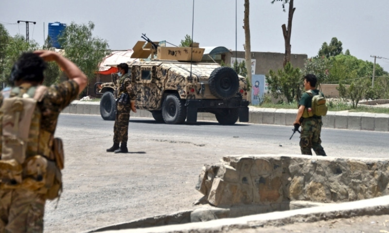 Afghan security personnel stand guard along the road amid fighting between Afghan security forces and Taliban fighters in Kandahar on July 9. — AFP