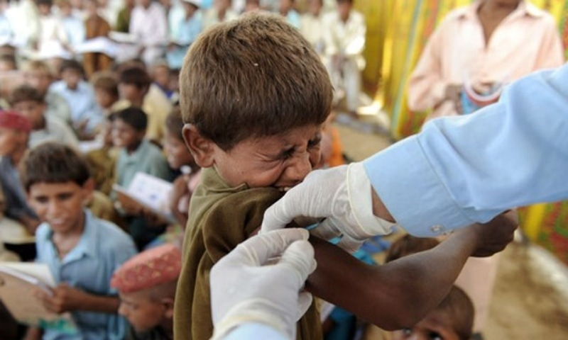 In this file photo, a health worker gives a hepatitis vaccination  to a flood affected boy at a makeshift school on higher ground in southern Sindh. — AFP