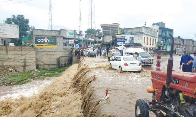 Vehicles pass through a flooded road in Lower Dir after heavy rain on Wednesday. — INP