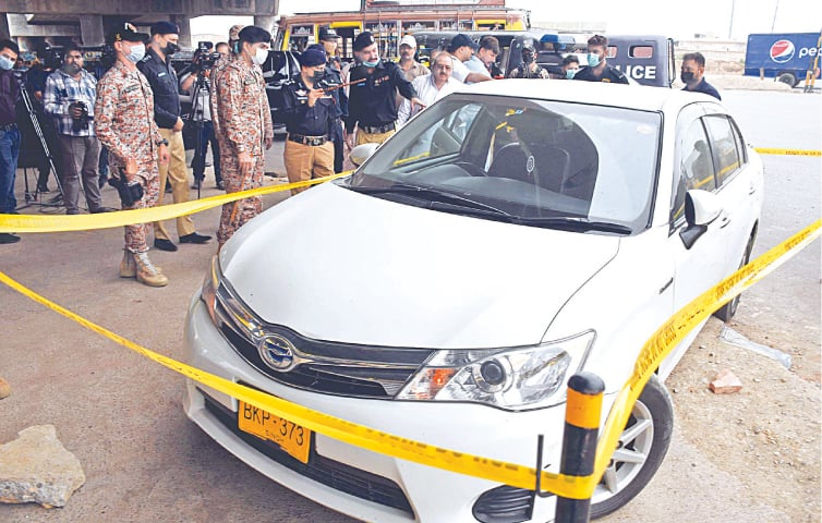 POLICE and Rangers officials inspect the car the Chinese national was riding near Gulbai bridge on Wednesday.—Online