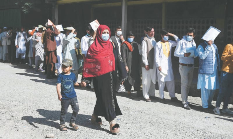 A WOMAN and a child walk past people standing in a queue to submit their passport applications at an office in Kabul.—AFP
