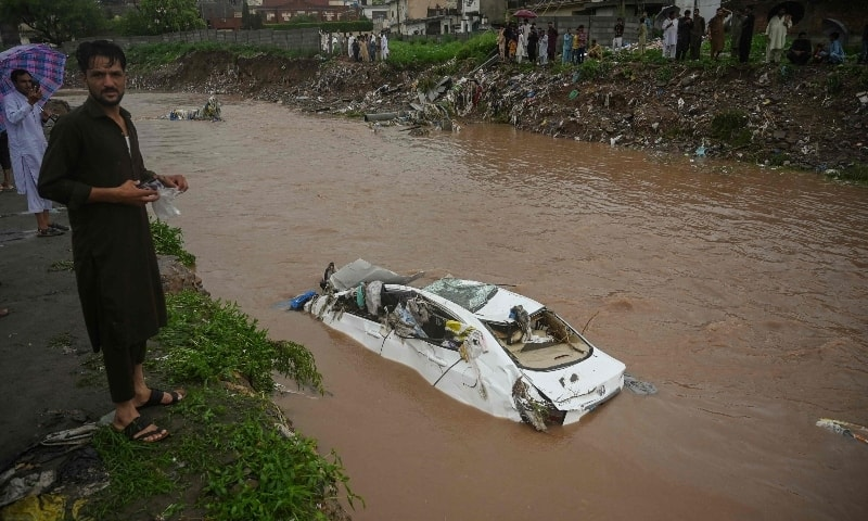 Residents gather as they look at a damaged car submerged in the flood waters after heavy monsoon rains in Islamabad on July 28. — AFP