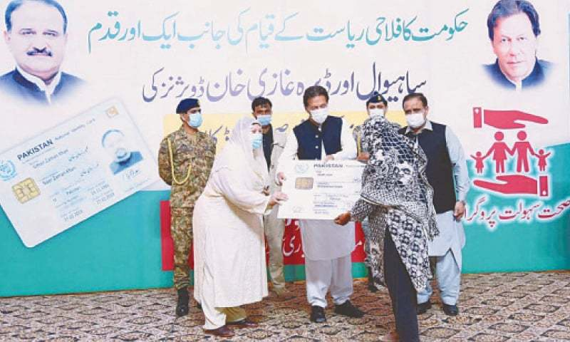 In this file photo, Prime Minister Imran Khan and Punjab Health Minister Dr Yasmin Rashid distribute health insurance cards among the people of Sahiwal and Dera Ghazi Khan divisions. — APP