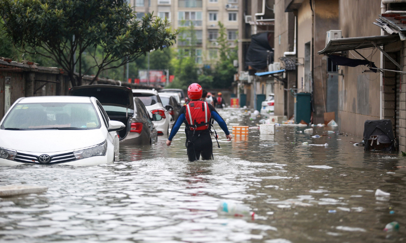 A rescuer walks down a flooded area on Wednesday in Yangzhou, in China's eastern Jiangsu province, after heavy rains brought by the passage of Typhoon In-Fa inundated the eastern coast of China. — AFP