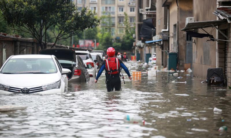 چین میں سیلاب کے بعد یینگ ژو شہر میں ایک ریسکیو اہلکار کو گھٹوں تک پانی میں چلتے دیکھا جا سکتا ہے— فوٹو: اے ایف پی