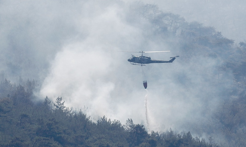 AN army helicopter dropping water over a forest fire near Qobayat village, in the northern Akkar province of Lebanon, on Thursday.—AP