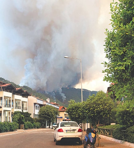 SMOKE rises from a forest fire close to a hotel in the Aegean coastal town of Marmaris.—AP