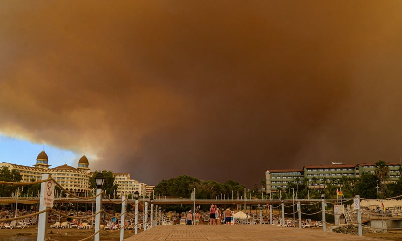 Dark smoke drifts over a hotel complex during a massive forest fire which engulfed a Mediterranean resort region on Turkey's southern coast near the town of Manavgat. — AFP
