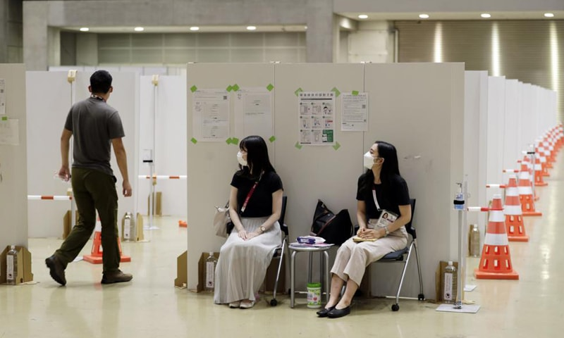 Workers (centre) help direct a man into a booth for a coronavirus infection test at the Main Press Centre for the Olympics. — AP