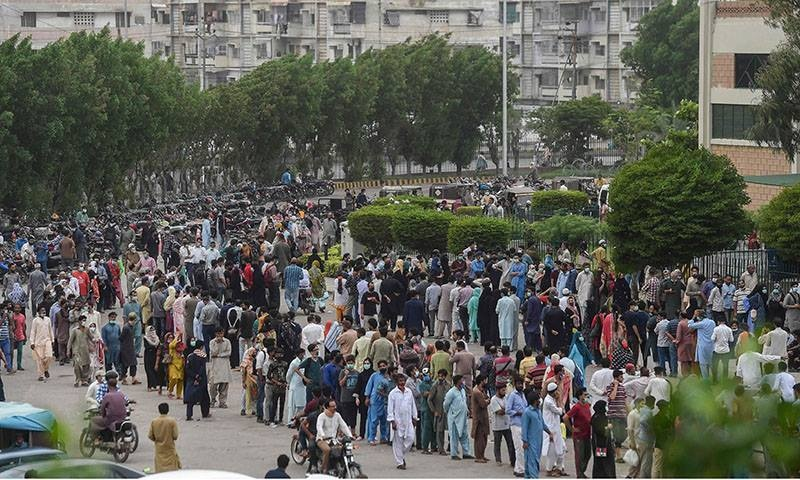 People gather in large numbers and queue up to register themselves and get inoculated with the Covid-19 vaccine at a vaccination centre in Karachi on July 29. — AFP