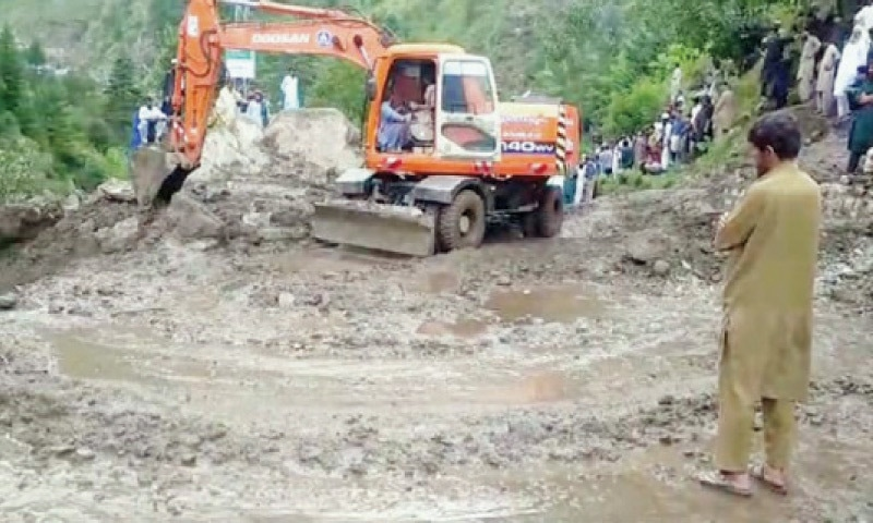 A machine removes a mass of mud from the MNJ Road in Mahandri area of Kaghan valley on Friday. — Dawn