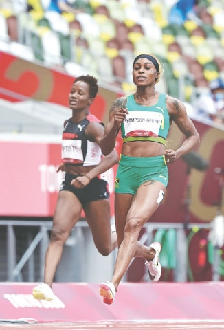 JAMAICA'S Elaine Thompson-Herah (R) competes in the women's 100m heats at the Olympic Stadium on Friday.—AFP