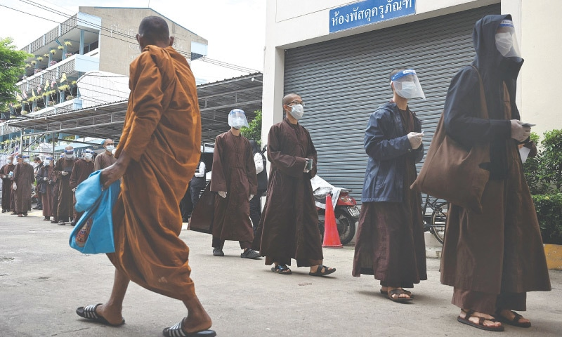 BANGKOK: Buddhist monks from Vietnam queue up to receive doses of a Covid-19 vaccine at a vaccination centre on Friday. — AFP
