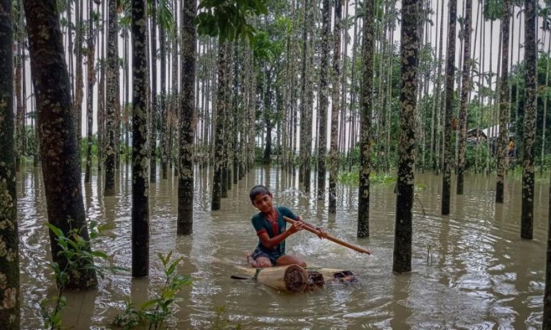 A child wades through a flooded area using a makeshift raft at Maulovir Para, Cox's Bazar, Bangladesh on Friday. — AFP