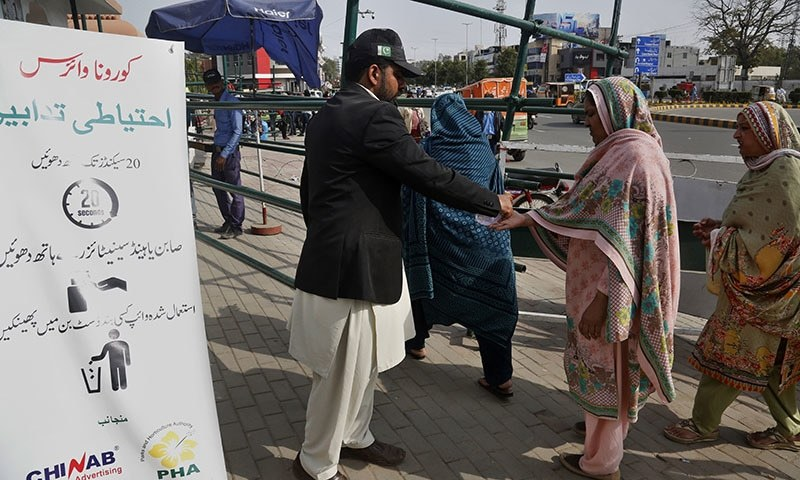 A worker provides sanitizer to visitors outside a park next to a banner informing precautions about the coronavirus in Lahore. — AP/File
