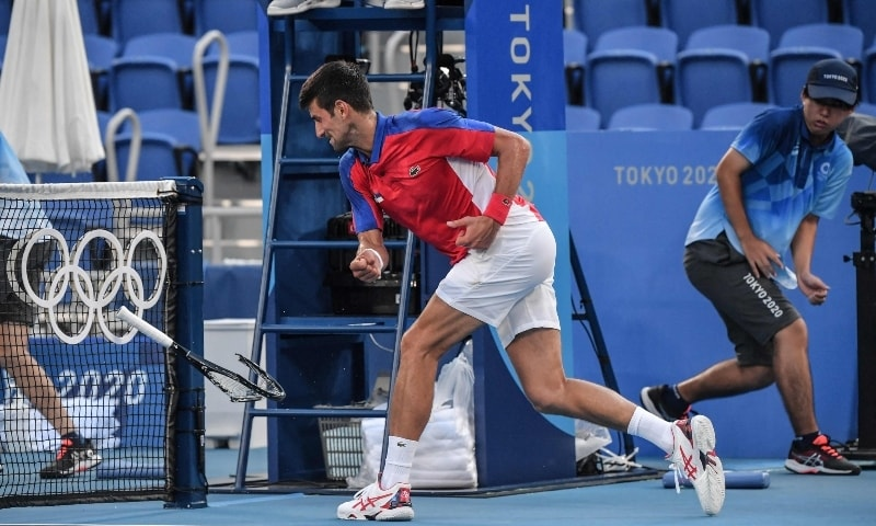 Serbia's Novak Djokovic smashes his racket during his Tokyo 2020 Olympic Games men's singles tennis match for the bronze medal against Spain's Pablo Carreno Busta on July 31. — AFP
