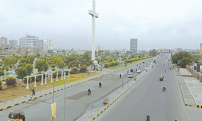 KARACHI: Light traffic moves along a road on Saturday due to a partial lockdown aimed to help control the spread of the coronavirus  in the city.—AP